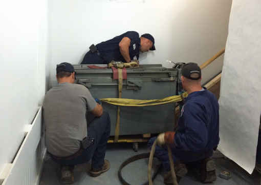 Movers securing the Vandercook before taking it up the stairs.